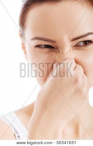 Beautiful woman with grimace beacuse of bad smell. Isolated on white.