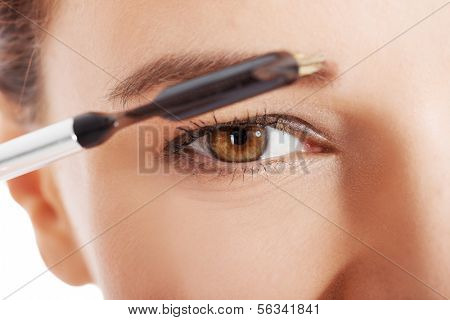 Beautiful woman brushing her eyebrow. Close up.