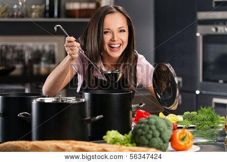 Cheerful young woman in apron on modern kitchen will ladle tasting from pot