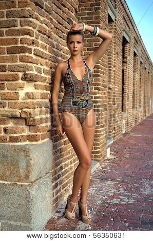 Swimsuit model posing sexy in front of old fort
