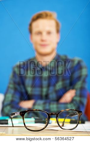 Pair of horn rimmed glasses on a graphic designer's desk. Shallow Depth of Field, focus on the glasses.