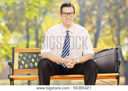 Relaxed young businessman sitting on a bench and looking at camera in a park