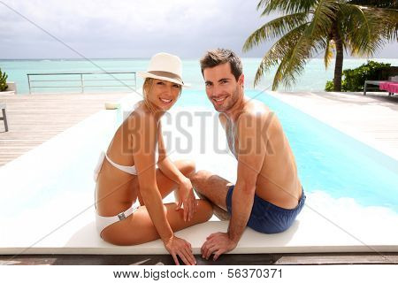 Couple sitting by infinity pool in tropical island