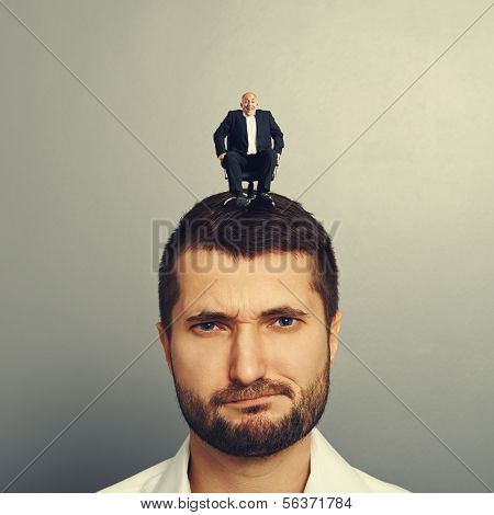 portrait of displeased man with small boss on the head