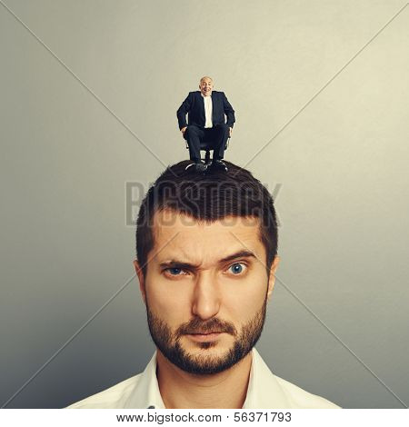 portrait of dissatisfied man with small man on the head