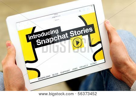 Venice,California-Jan 03:Man holding a tablet computer with opened homepage of Snapchat.com.Snapchat said it will release a new version of its app after hackers attack on January 3,2014 in Venice,USA.
