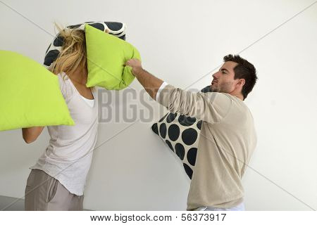 Angry couple throwing pillows at each other