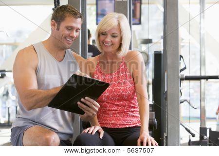 Entrenador personal hablando con la mujer en el gimnasio