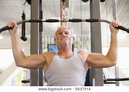 Man Weight Training At Gym
