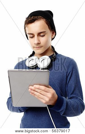 Trendy Teenager With Cap And Headphones Around The Neck  Working On A Tablet