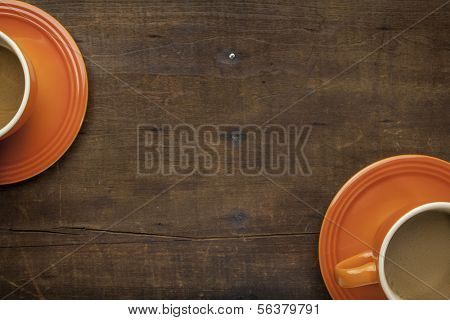 orange stoneware coffee cups on a grunge weathered wooden table with a copy space