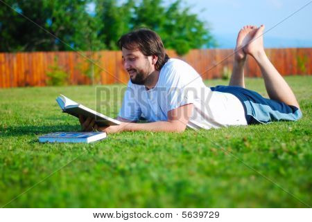 Young Man Is Laying On Green Ground And Learning