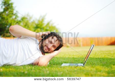 Young Man Is Laying On Green Ground And Taking A Nice Time