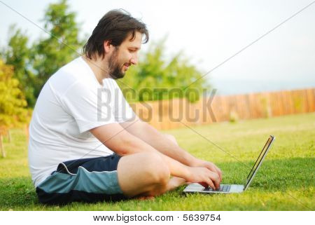 Young Man Is Sitting On Green Ground And Taking A Nice Time