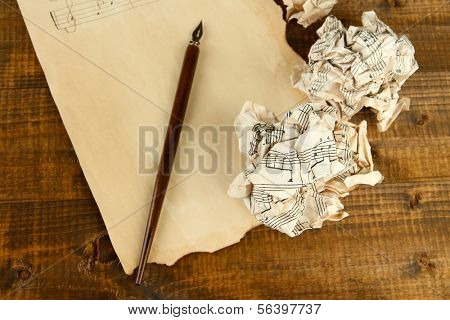 Crumpled paper balls with ink pen and music sheet on wooden background
