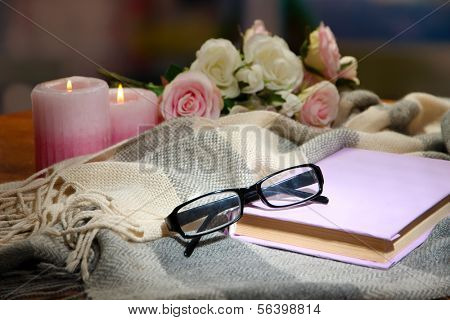 Composition with old book, eye glasses, candles and plaid on dark background
