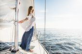 stock photo of sailing vessel  - woman staying on the sailboat during sunset - JPG