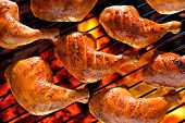 foto of thighs  - Grilled chicken thigh on the flaming grill - JPG
