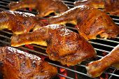 stock photo of barbecue grill  - Grilled chicken thigh on the flaming grill - JPG