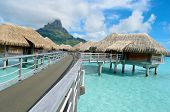 image of french polynesia  - Luxury overwater bungalows in a vacation resort in the clear blue lagoon with a view on the tropical island of Bora Bora near Tahiti in French Polynesia - JPG