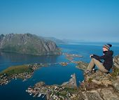 stock photo of reining  - Woman hiker looking at Reine village panorama - JPG