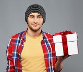 stock photo of beanie hat  - Stylish young man in shirt and beanie hat with gift box - JPG