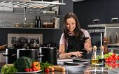 stock photo of apron  - Cheerful young woman in apron on modern kitchen with cookbook and glass of wine - JPG