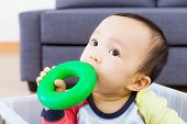 stock photo of love bite  - Asian baby boy bite toy - JPG