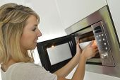 picture of oven  - Woman at home using microwave oven - JPG