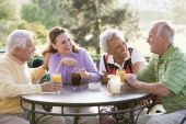 stock photo of senior adult  - Friends Enjoying A Beverage By A Golf Course - JPG
