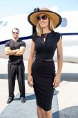 image of bodyguard  - Happy woman in elegant dress with bodyguard and private jet in background - JPG