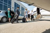 foto of jet  - Airhostess and pilot greeting business people before boarding private jet - JPG