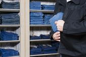 pic of shoplifting  - jeans being stolen by a shoplifter in a shop - JPG