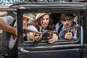 stock photo of tommy-gun  - Vintage gangsters shooting machine guns from car door