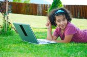 A Little Cute Girl Laying Down In Grass With Laptop