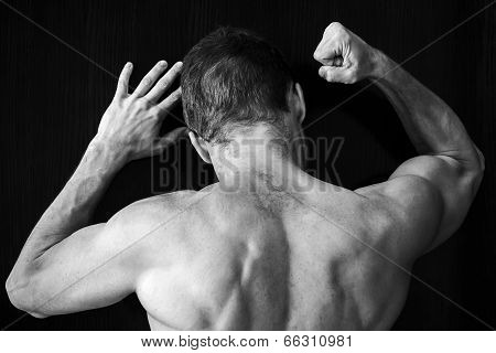 Strong Muscular Young Caucasian Man Knocks On Black Wall With His Fist