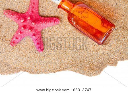 starfish and bottle with letter on sand