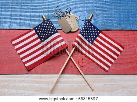 Two crossed American flags on a red, white and blue wood table with military dog tags. Great concept image for the 4th of July, Memorial Day,  Veterans Day or military projects.
