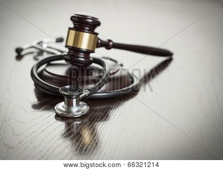 Gavel and Stethoscope on Reflective Wooden Table.