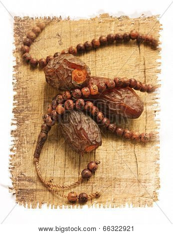 dates and islamic rosary image on papyrus paper texture