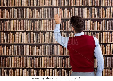 Young man in library take book from shelf