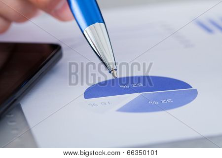 Hand Holding Pen On Graph