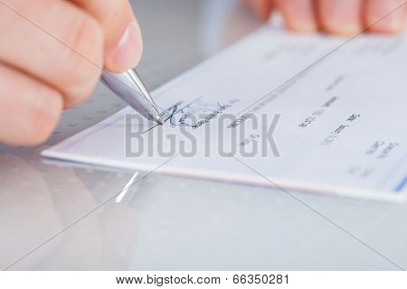 Hand With Pen Over Checkbook