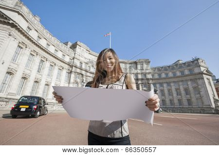 Portrait of happy young woman holding map against Admiralty Arch in London; England; UK