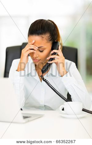 tired businesswoman using landline phone in office