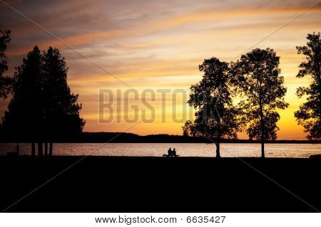 Elderly Couple Sitting On A Bench By Lake At Sunset