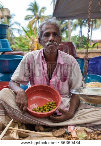 HIKKADUWA, SRI LANKA - FEBRUARY 23, 2014: Local street vendor selling olives. The Sunday market is a fantastic way to see Hikkaduwa's local life come alive along with fresh produce and local delicacy