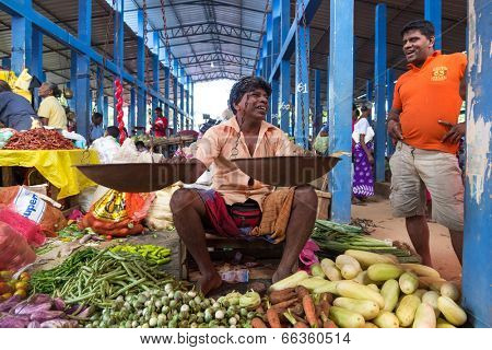 HIKKADUWA, SRI LANKA - FEBRUARY 23, 2014: Local street vendor selling vegetables. The Sunday market is great way to see Hikkaduwa's local life come alive along with fresh produce and local delicacy