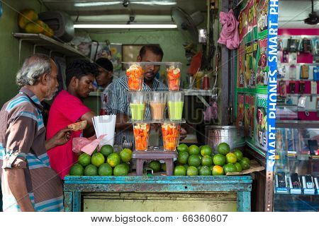 COLOMBO, SRI LANKA - FEBRUARY 22, 2014: Local man buying fruit juice from one of many street vendor in the city.