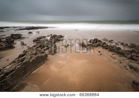 Long Exposure Landscape Beach Scene With Moody Sky